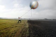 Man and Balloon. Man is Holding a Balloon on Grass Field Stock Photo