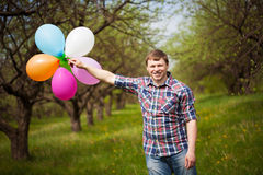 Man with balloons on the green spring meadow Royalty Free Stock Image