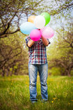 Man with balloons on the green spring meadow Royalty Free Stock Photography