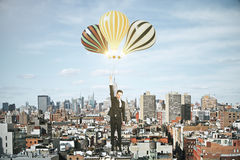 Man with baloons above megapolis city concept Royalty Free Stock Photo