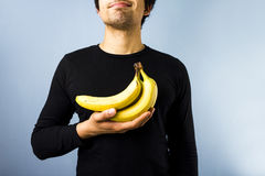 Man with bananans. Young multiracial man holding a bunch of bananas Royalty Free Stock Images