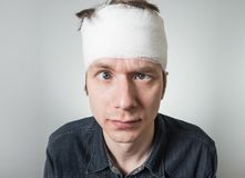 Man with bandage on his head. Cockeyed young guy with bandage on his head. Image related with treatment of the wounds Royalty Free Stock Photo