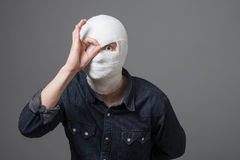 Man with bandage on his head. Injured young guy after surgery with bandage all over his face with one eye opened showing searching sign. Image related with stock photos