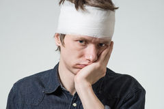 Man with bandage on his head. Injured young man with bandage on his head holding cheek by hand. Image related with treatment of the wounds Stock Photography