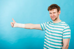 Man with bandaged hand showing thumb up. Stock Photography
