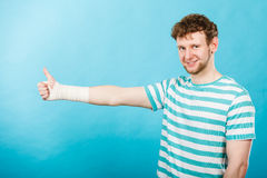 Man with bandaged hand showing thumb up. Stock Photos