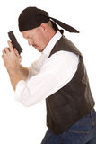 Man bandana gun side look down. A man in a bandana and black vest holding a gun looking down Royalty Free Stock Images