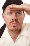 Man bandana hand on brow looking. A man in a bandana hand above eyes looking Stock Image