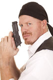 Man bandana on head gun close look smirk. A man with a gun in his hands looking Stock Image