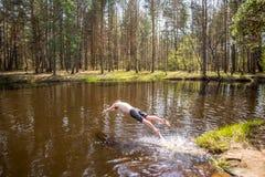 Man banhoppningen in i vatten fotografering för bildbyråer