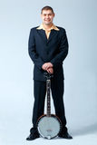 Man With Banjo. Man in dark suit standing with banjo, full length Royalty Free Stock Photo