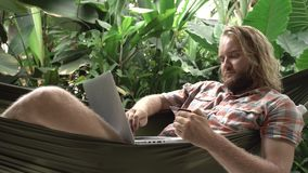 Man banking online with laptop while sitting on hammock. Man banking online with credit card and laptop while sitting on hammock, exotic background stock video