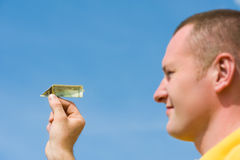 Man with banknote paper plane. Man with banknote plane focus at latter royalty free stock photo