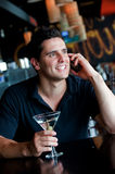 Man In Bar. A young man sitting in a bar with a martini and phone Royalty Free Stock Photography