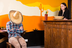A man in a bar got drunk and fell asleep sitting on a chair and. A men in a bar got drunk and fell asleep sitting on a chair and covered his face with a sombrero royalty free stock photo