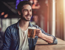 Man in bar. Handsome young man is drinking beer in bar and smiling Royalty Free Stock Photography