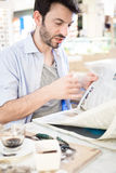 Man at the bar reading newspaper Stock Photography