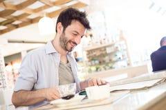 Man at the bar reading newspaper Royalty Free Stock Image