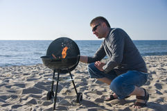 Man and barbecue on beach Stock Photo