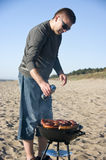 Man and barbecue on beach. A handsome man and a barbecue on the beach. He is pouring some beer from a can on the sausages Stock Images
