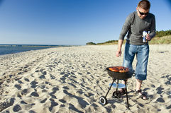 Man and barbecue on beach. A handsome man and a barbecue on the beach. He is checking if the sausages are done, holding a beer can in his hands Royalty Free Stock Photography