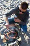 Man and barbecue on beach. A handsome man and a barbecue on the beach. He is checking if the sausages are done, holding a beer can in his hands Royalty Free Stock Image