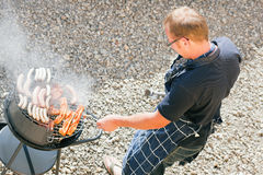 Man at the barbecue grill. Man preparing meat and sausages using a barbecue grill Stock Image