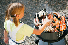 Man at the barbecue grill. Little girl preparing meat and sausages using a barbecue grill Stock Images