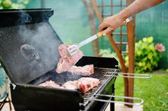 Man at a barbecue grill preparing meat for a garden party. Man hand at a barbecue grill preparing meat for a garden party Stock Photo