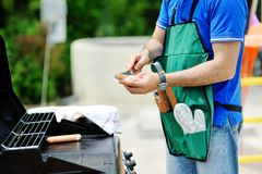 Man at the barbecue grill preparing sausages Royalty Free Stock Images