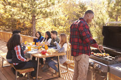 Man barbecues for friends at a table, on a deck in a forest Stock Images