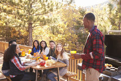 Man barbecuing on a deck talks to friends sitting at a table Royalty Free Stock Photography