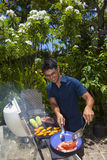 Man barbecuing in his garden Royalty Free Stock Photography