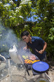 Man barbecuing in his garden Royalty Free Stock Photos