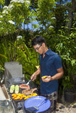 Man barbecuing in his garden Stock Photography