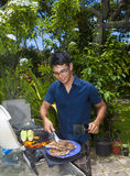 Man barbecuing in his garden Stock Photo