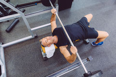 Man with barbell on a bench press training Stock Image