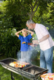 Man by barbeque showing son (9-11) sausage, smiling Royalty Free Stock Photo