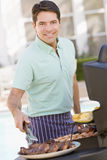 Man Barbequing In A Garden Stock Images