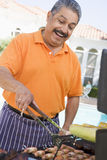 Man Barbequing In A Garden Royalty Free Stock Photo