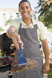 Man Barbequing In A Garden Stock Image