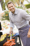 Man Barbequing In A Garden Stock Photo