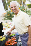 Man Barbequing In A Garden Royalty Free Stock Photos