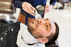 Man and barber applying shaving foam to beard Stock Photo