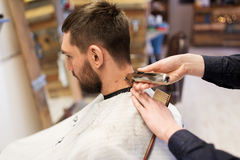 Man and barber hands with trimmer cutting hair Stock Image