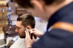 Man and barber hands with trimmer cutting hair Stock Images