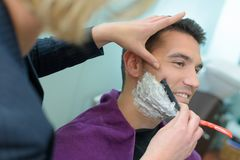 Man barber shaves customers beard. Man barber shaves a customers beard stock photo