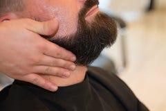 Man barber shaves his beard. At the barber shop royalty free stock image