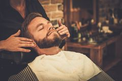 Man in a barber shop. Hairstylist applying after shaving lotion in barber shop Royalty Free Stock Image