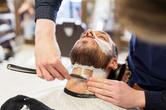 Man and barber with straight razor shaving beard Royalty Free Stock Images